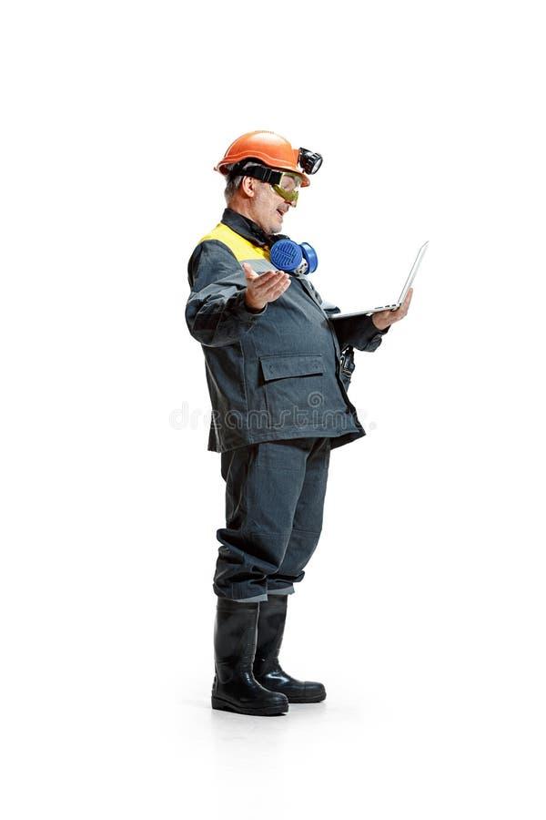 Lo studio ha sparato del minatore maschio barbuto senior felice che sta nella vista di profilo alla macchina fotografica con il c immagine stock