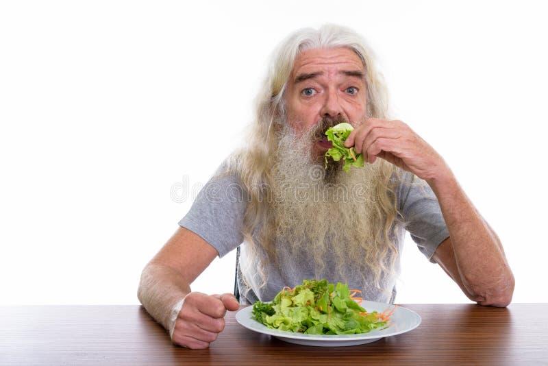 Lo studio ha sparato del piatto mangiatore di uomini barbuto senior di insalata su woode fotografia stock libera da diritti