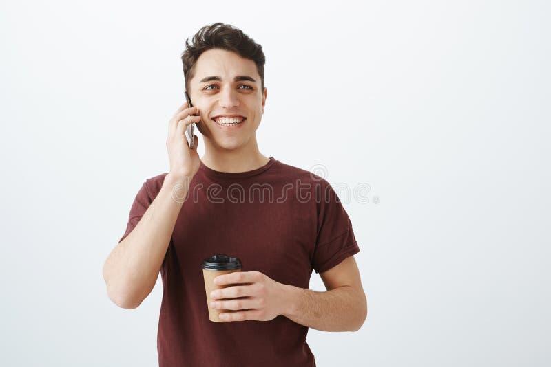 Lo studio ha sparato del tipo allegro bello, tenendo la tazza di caffè e parlando sullo smartphone, sorridendo largamente, essend fotografie stock