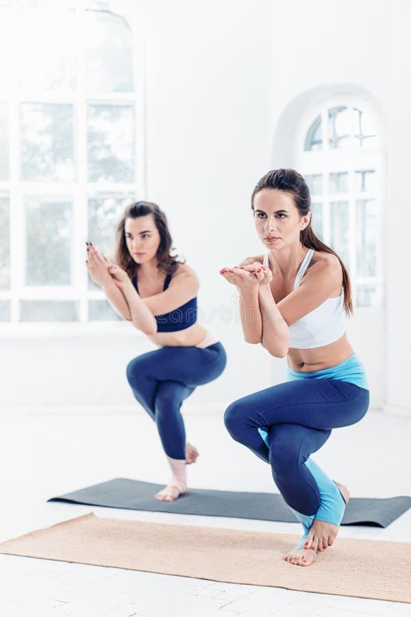 Lo studio ha sparato delle giovani donne che fanno gli esercizi di yoga su fondo bianco fotografie stock libere da diritti
