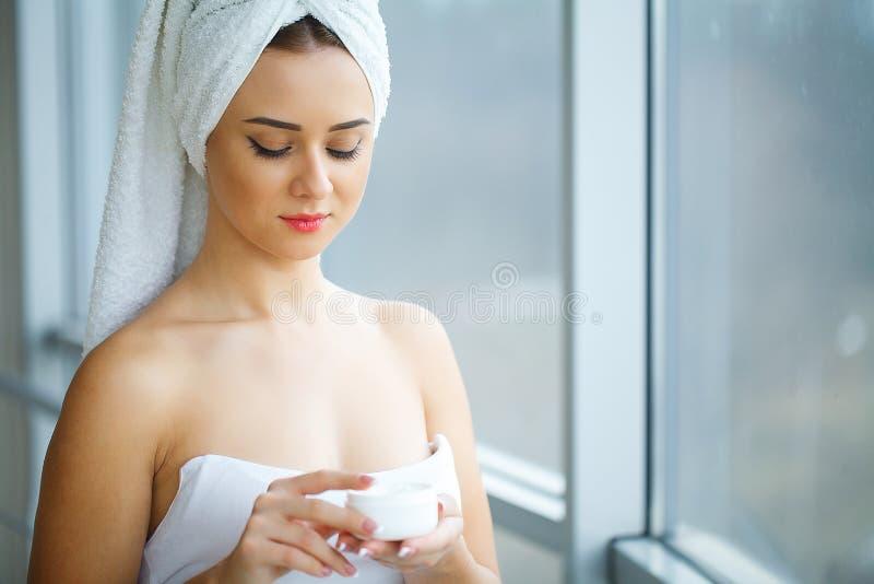 Lo studio ha sparato di bella giovane donna che applica la crema dell'idratante immagini stock