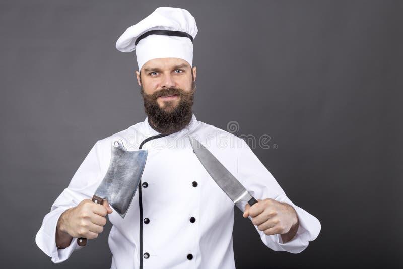 Lo studio ha sparato di giovane cuoco unico barbuto felice che tiene i coltelli taglienti immagini stock