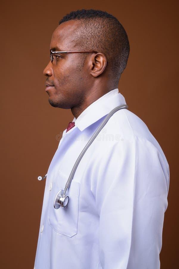 Lo studio ha sparato di giovane medico africano dell'uomo contro fondo marrone fotografia stock