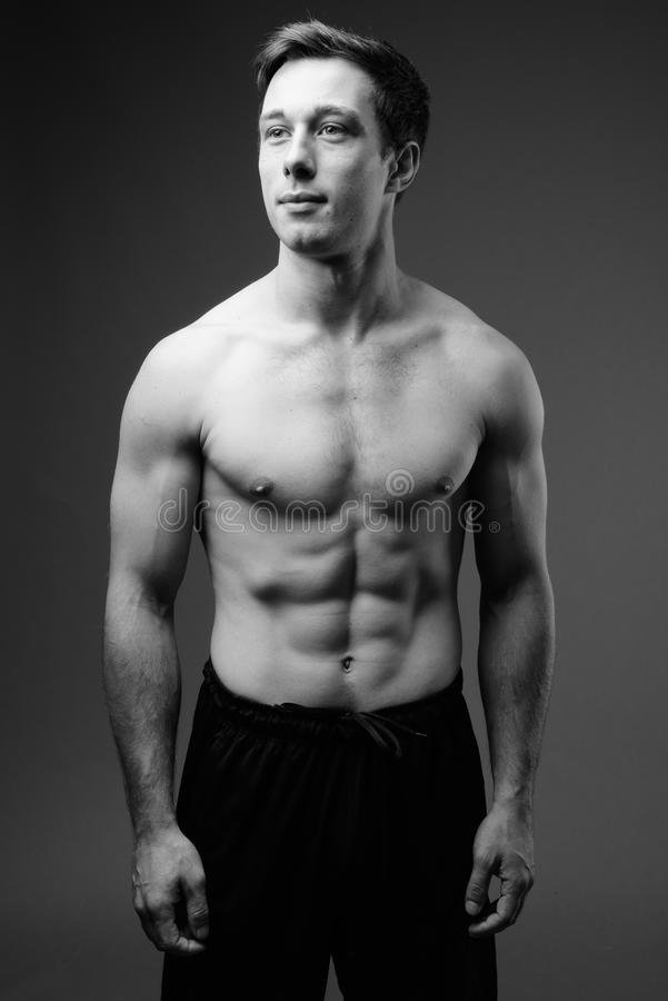 Lo studio ha sparato di giovane uomo bello muscolare senza camicia nel nero fotografia stock