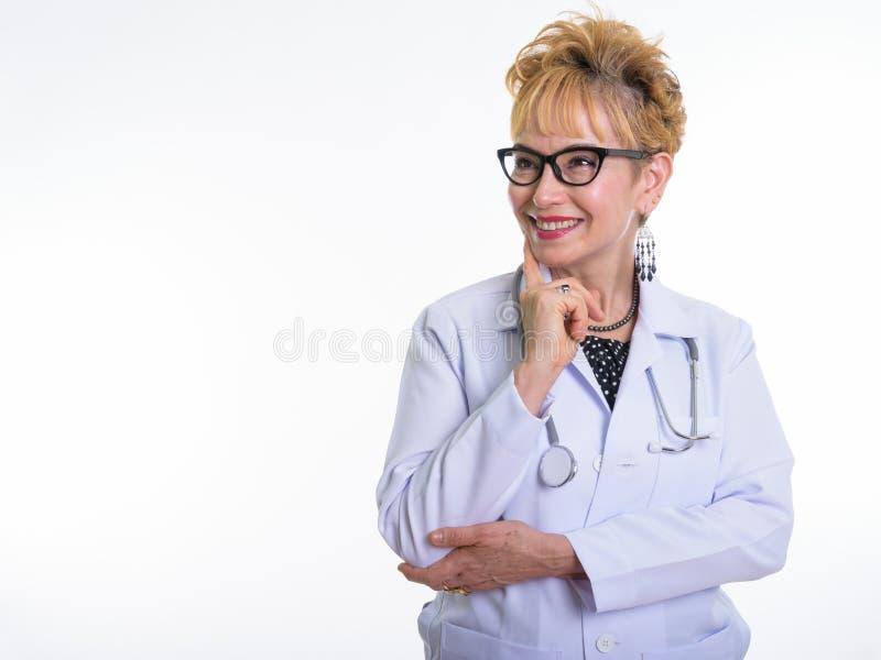 Lo studio ha sparato di medico asiatico senior felice della donna che sorride e pensa immagine stock libera da diritti