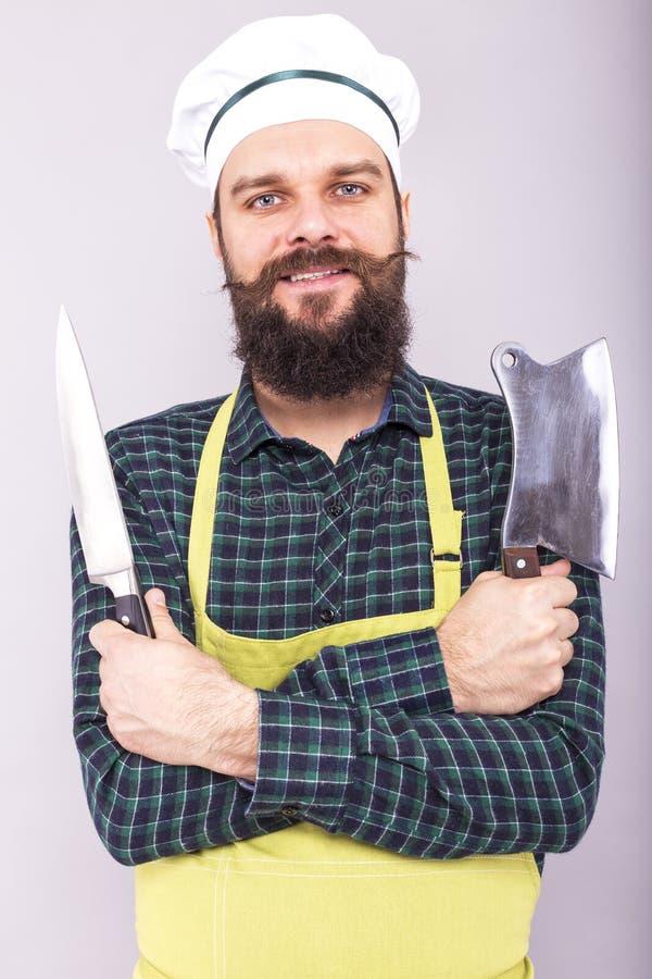 Lo studio ha sparato di un giovane barbuto felice che tiene i coltelli taglienti fotografia stock libera da diritti