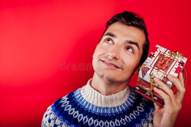Lo studio ha sparato di un giovane in maglione islandese che tiene un contenitore di regalo Concetto di celebrazione del nuovo an fotografia stock
