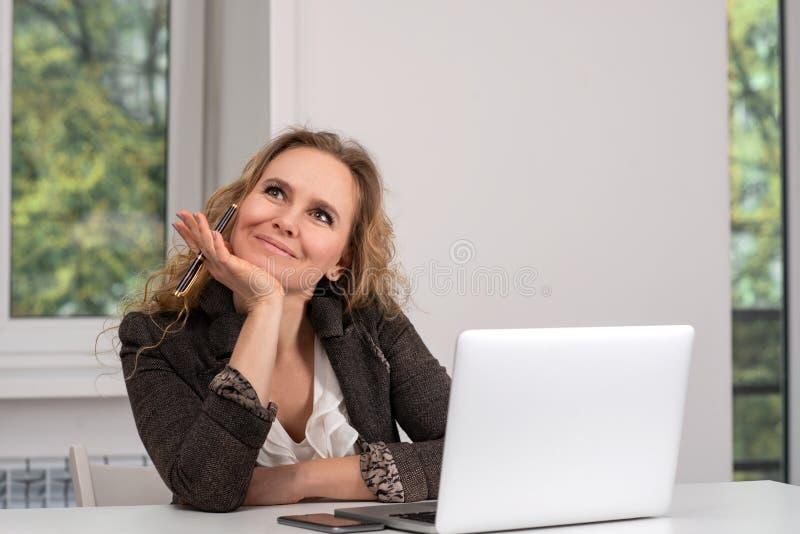 Lo studio ha sparato di un vestito d'uso del braun della donna che lavora al suo computer portatile e vago guarda al lato fotografia stock libera da diritti