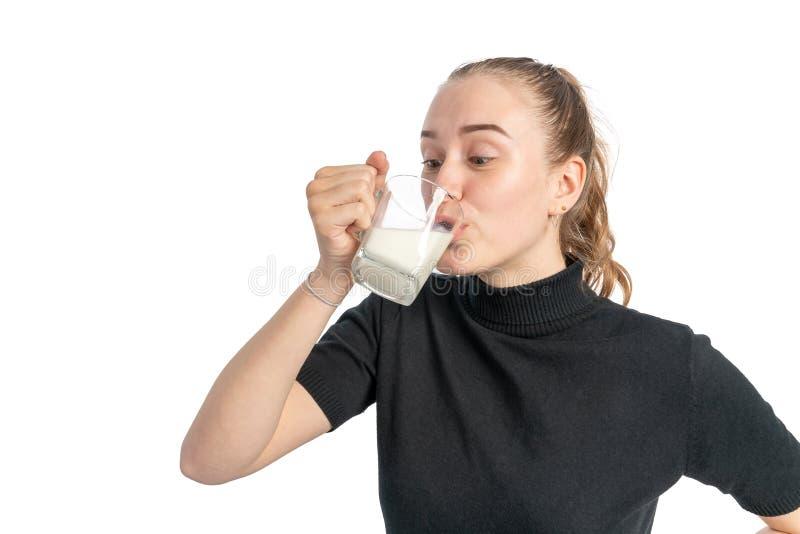 Lo studio ha sparato di una giovane donna tiene un bicchiere di latte e le bevande fotografia stock libera da diritti