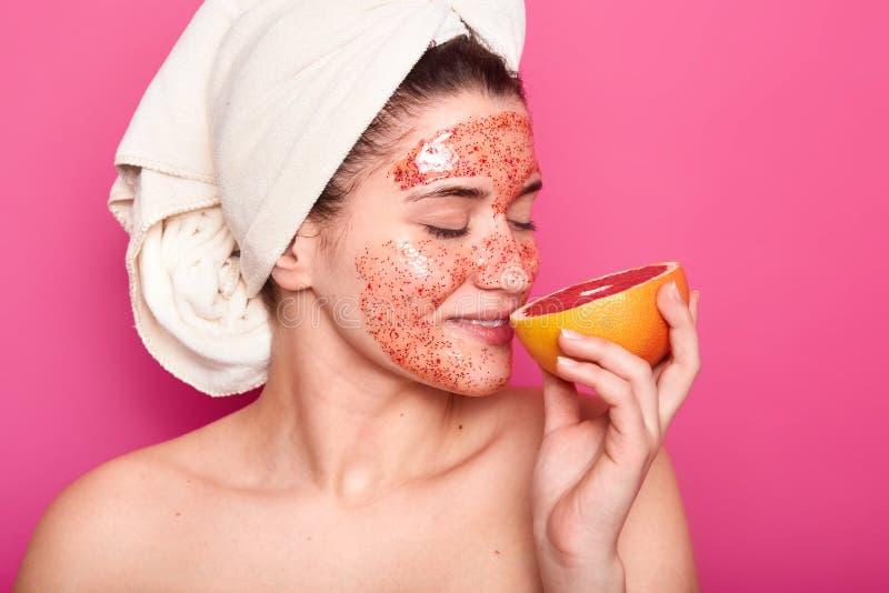 Lo studio sparato del pompelmo odorante sembrante piacevole della giovane donna europea, ha asciugamano bianco sulla testa, mostr immagini stock libere da diritti