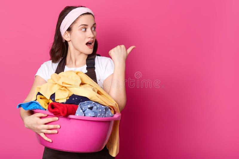 Lo studio sparato della casalinga della giovane donna con il bacino rosa, pronto per lavare le cose, indossa la banda dei capelli immagine stock libera da diritti