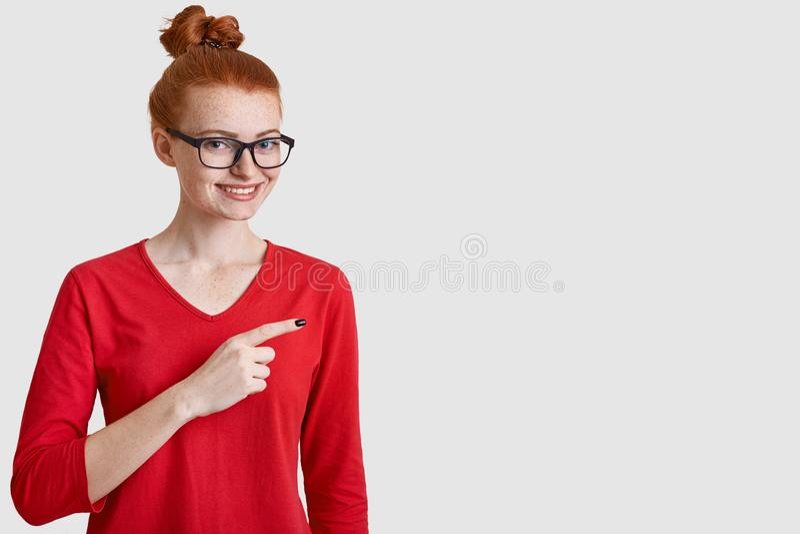 Lo studio sparato della donna allegra con il panino rosso dei capelli, indossa gli occhiali, abbigliamento casual, punti da parte fotografia stock libera da diritti