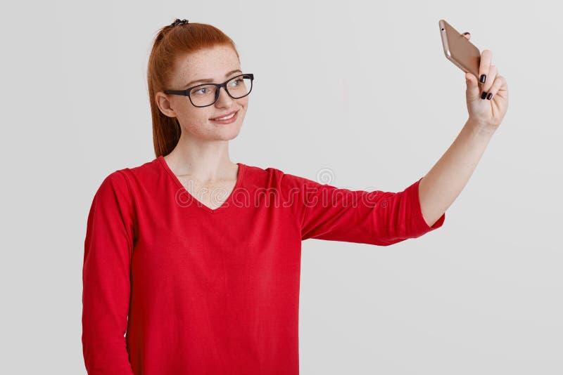 Lo studio sparato della femmina dai capelli rossi allegra in occhiali, fa il selfie sul telefono cellulare, posa in camera dell'a fotografia stock