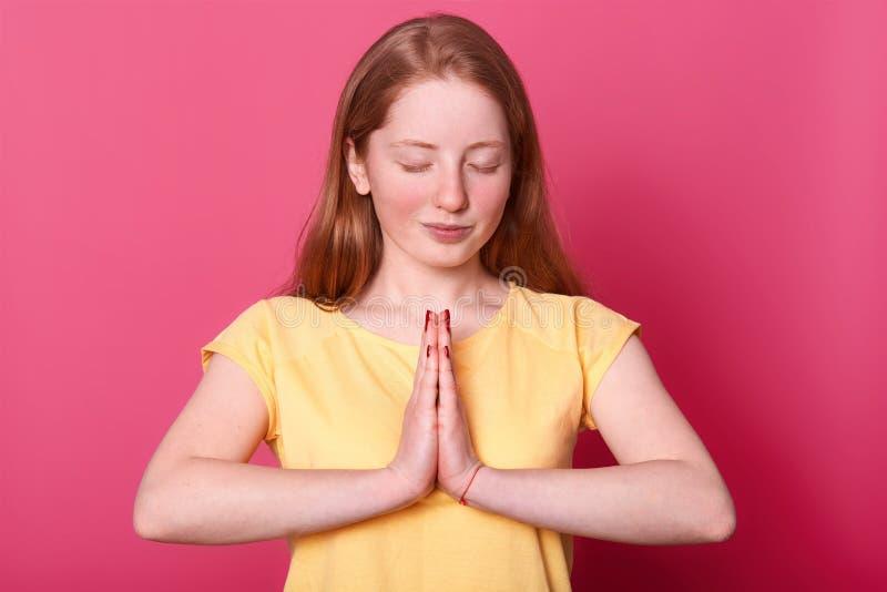 Lo studio sparato di bella ragazza caucasica calma dell'adolescente sta isolato sopra fondo rosa mentre prega, tiene gli occhi ch immagini stock libere da diritti