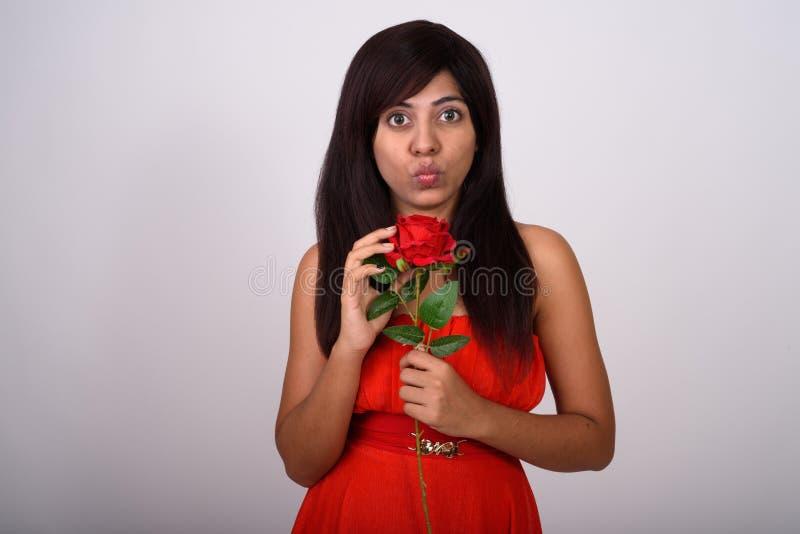 Lo studio sparato di giovane attimo persiano della rosa rossa della tenuta della donna si increspa immagini stock libere da diritti