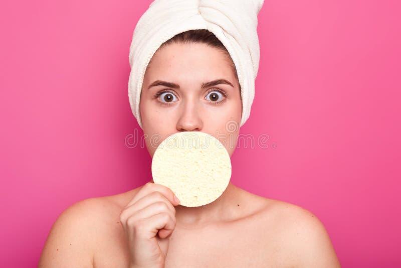 Lo studio sparato di giovane donna europea sembrante piacevole copre la bocca di spugna, ha asciugamano bianco sulla testa Modell immagine stock