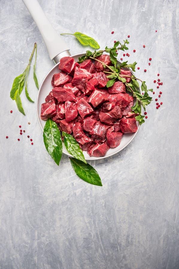 Lo stufato di manzo ha preparato per goulash che cucina in pentola bianca con condimento e le spezie freschi, vista superiore immagini stock libere da diritti