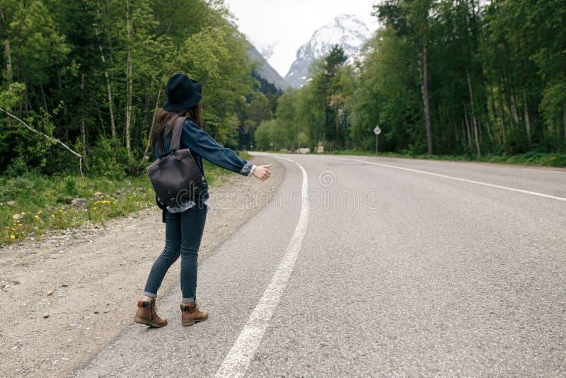 Lo zaino felice della ragazza nei precedenti della foresta e della strada, si rilassa il tempo sul viaggio di concetto di festa,  immagini stock libere da diritti