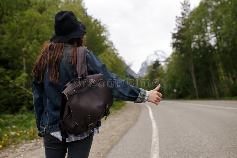 Lo zaino felice della ragazza nei precedenti della foresta e della strada, si rilassa il tempo sul viaggio di concetto di festa,  immagini stock