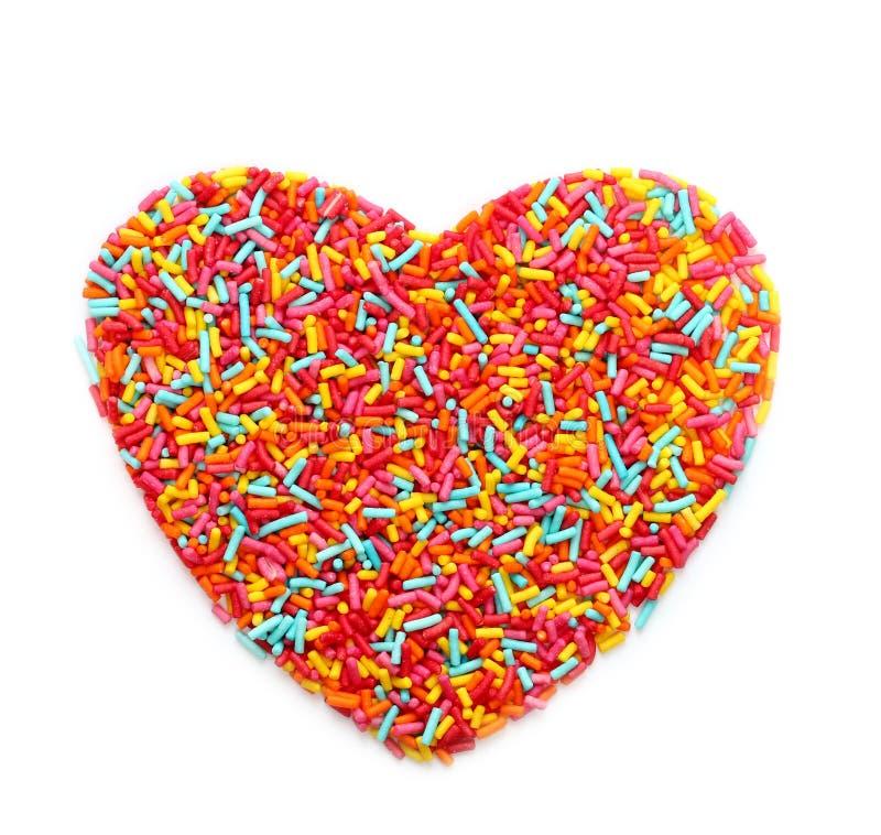 Lo zucchero spruzza il cuore a forma di isolato su bianco fotografia stock libera da diritti