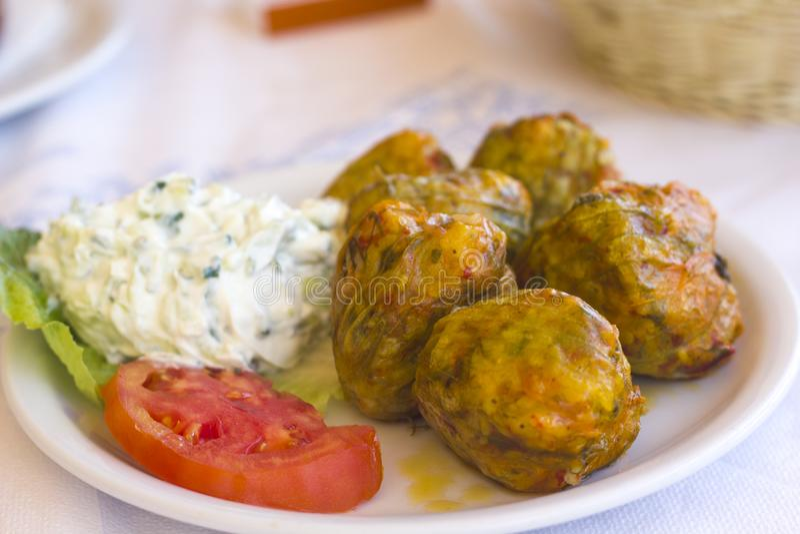 Lo zucchini farcito tradizionale greco fiorisce su un piatto bianco fotografia stock