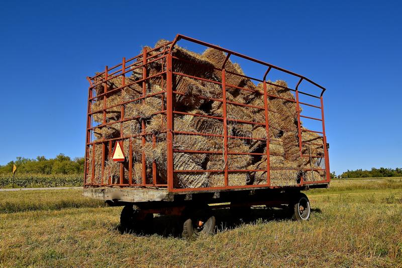 Bales in a caged hay rack. A load of baled straw in a hay wagon is parked in a field of wheat stubble stock images