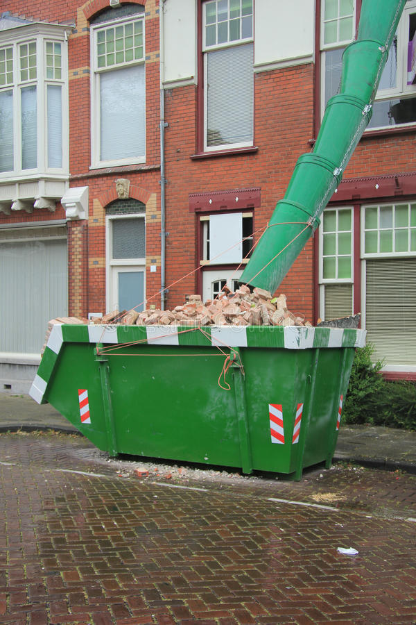 Loaded dumpster. Near a construction site, home renovation stock images