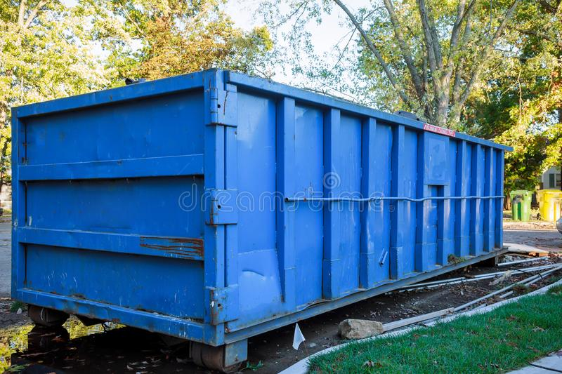 Roll-off dumpster filled with building rubble. Loaded dumpster near a construction site, home renovation dumpster filled with building rubble dumpster royalty free stock image
