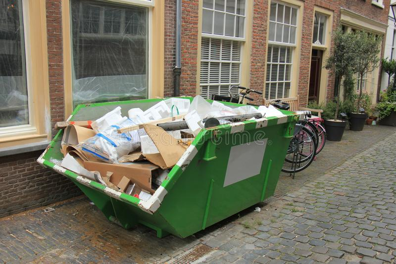 Loaded dumpster. Near a construction site, home renovation royalty free stock photography