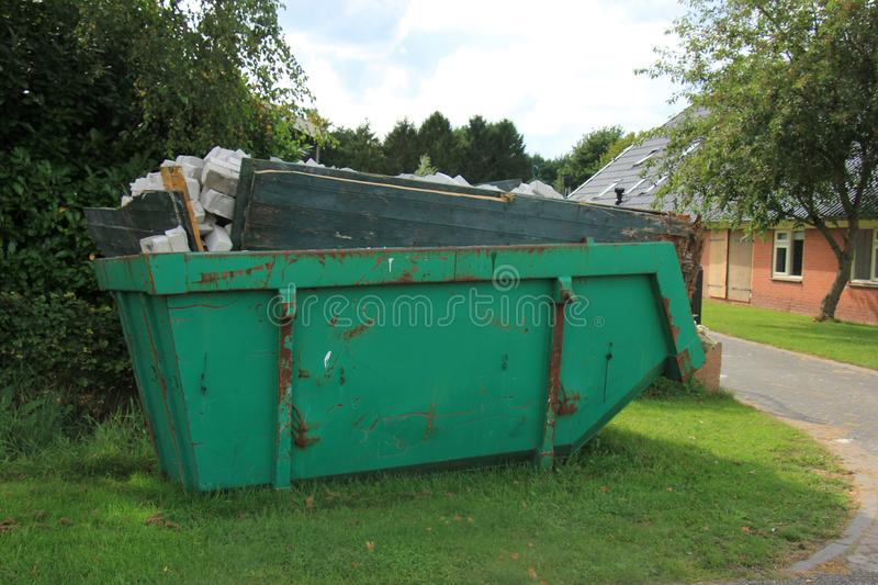 Loaded garbage dumpster. Loaded dumpster near a construction site, home renovation royalty free stock image