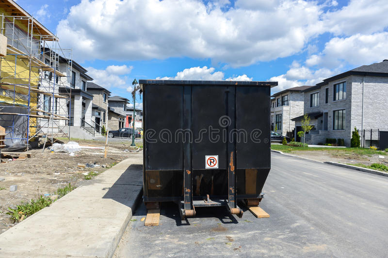 Loaded dumpster near a construction site. Home renovation in Montreal Bois-franc royalty free stock photo
