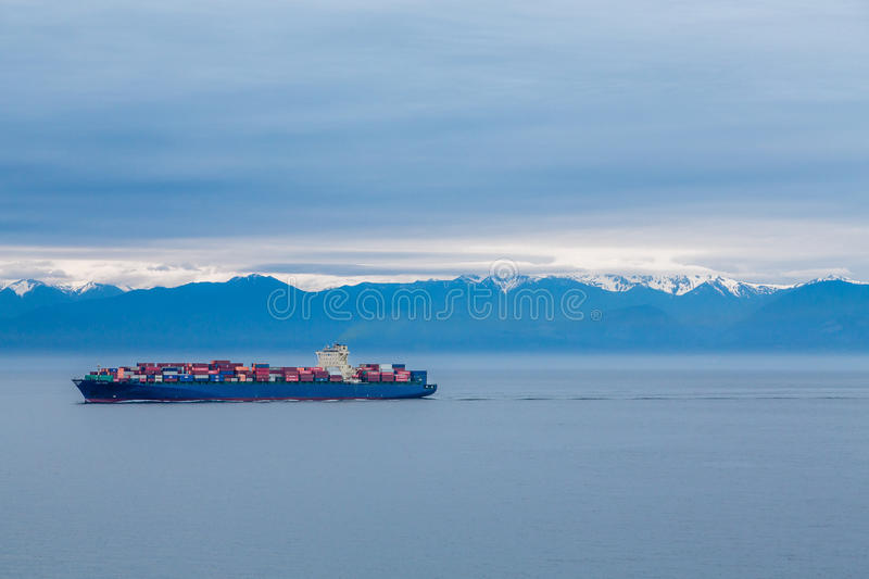 Loaded Freighter Under Blue Mountains stock photo