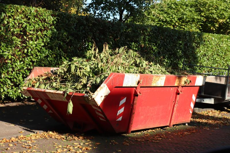 Loaded garbage dumpster. Loaded dumpster or disposal bin loaded with garden rubbish stock photo