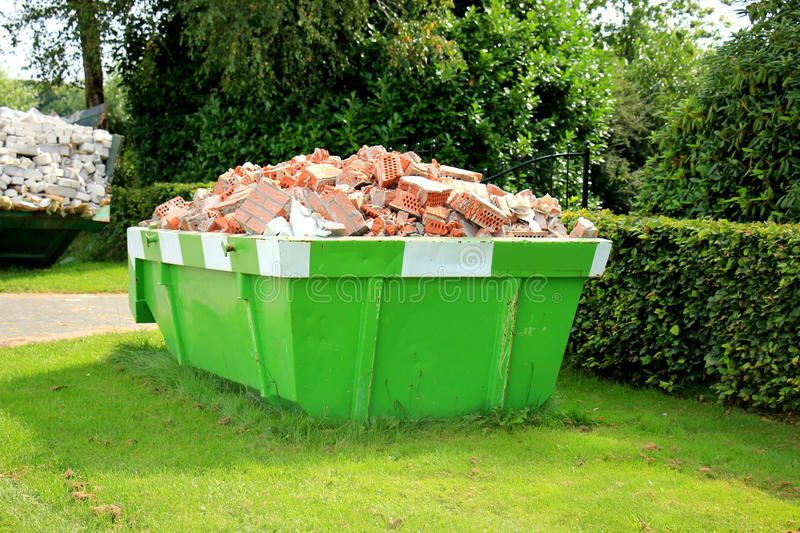 Loaded garbage dumpster. Loaded dumpster near a construction site, home renovation stock photography