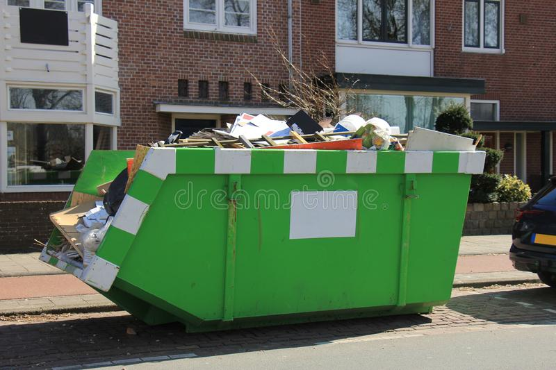 Loaded garbage dumpster. Loaded dumpster near a construction site, a home renovation or maintenance stock photo