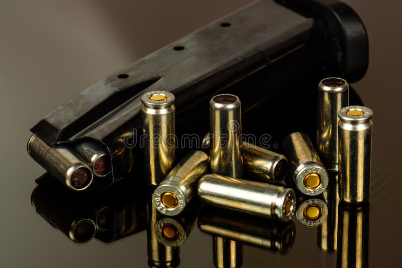 The loaded holder for the gun and cartridges against. A dark background stock photo