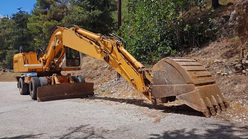 Loader excavator big yellow on forest road royalty free stock photography