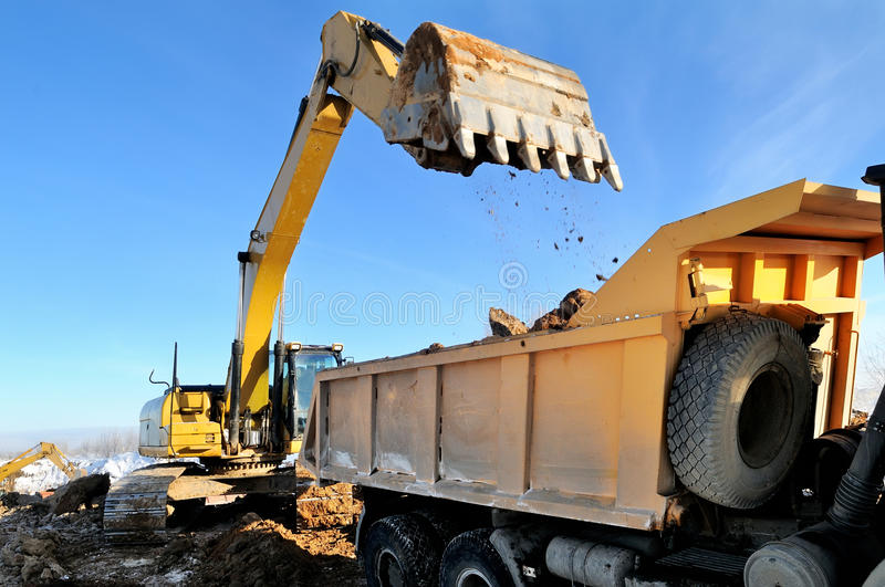 Loader excavator loading earth royalty free stock images