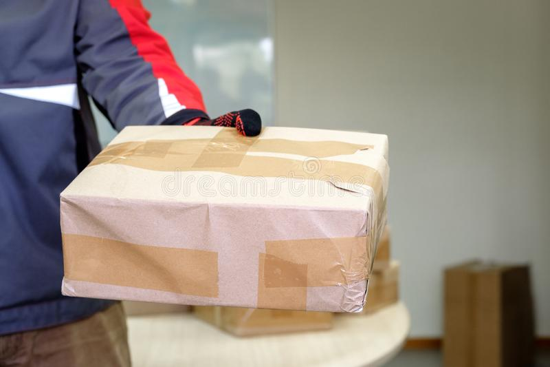 The loader holds a pack closed in the package with one hand. Delivery of the parcel stock photos