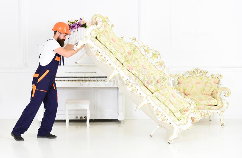 Loader moves sofa, couch. Man with beard, worker in overalls and helmet lifts up sofa, white background. Delivery. Service concept. Courier delivers furniture royalty free stock photography