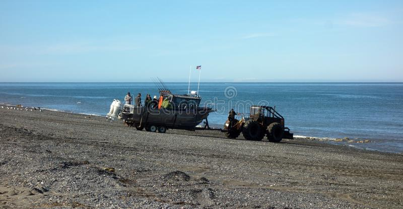 A boat being launched with machinery as seen at low tide in alaska stock photo