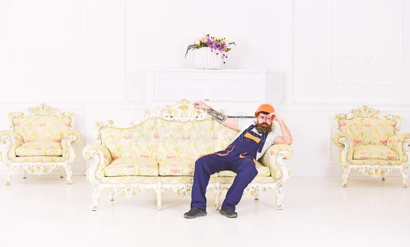 Loader sit on sofa, having rest. Exhausted loader concept. Man with beard, worker in overalls and helmet sits on couch. Tired, white background. Courier stock photo