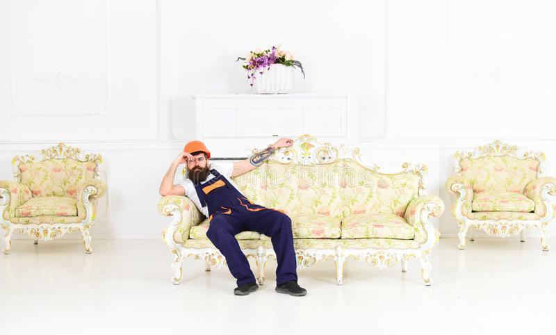Loader sit on sofa, having rest. Exhausted loader concept. Man with beard, worker in overalls and helmet sits on couch. Tired, white background. Courier stock images