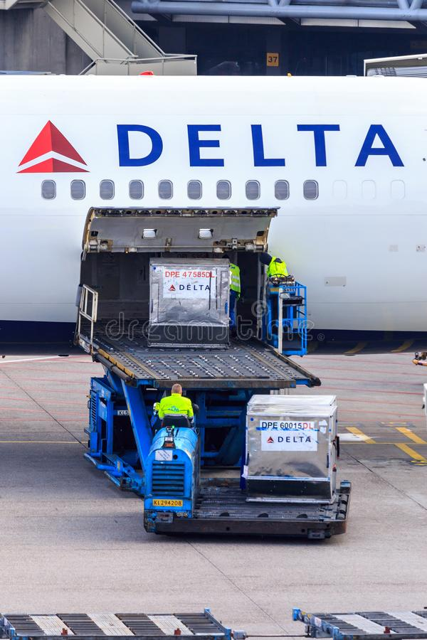 Loading air cargo containers. Air cargo containers are being loading onto a Delta Airlines passenger jet stock photography