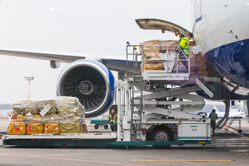 Loading cargo into the aircraft before departure stock photo