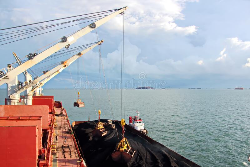 Loading coal from cargo barges onto a bulk carrier using ship cranes and grabs at the port of Samarinda, Indonesia. View of a close-up of the work of stock images