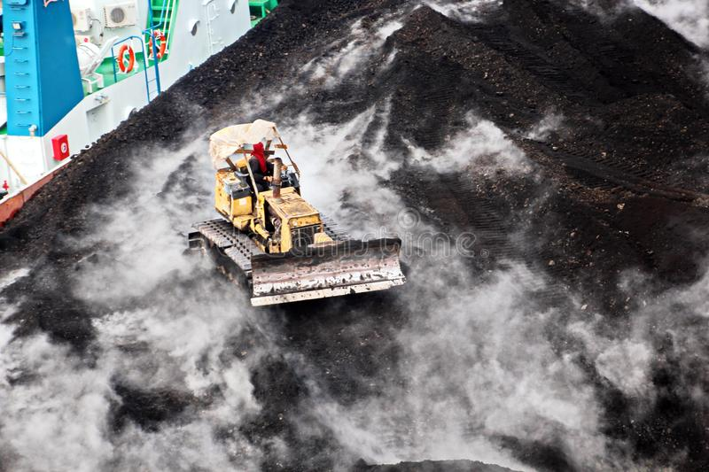 Loading coal from cargo barges onto a bulk carrier using ship cranes and grabs at the port of Samarinda, Indonesia. View of a close-up of the work of royalty free stock image
