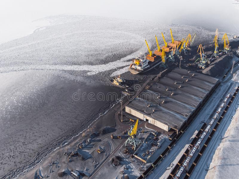 Loading coal mining in port on cargo tanker ship with crane bucket of train. Aerial top view royalty free stock images