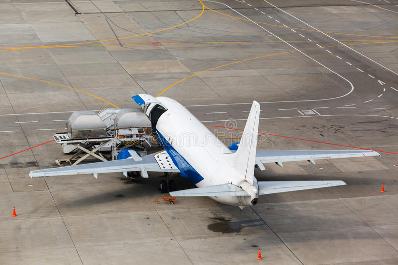 Loading containers in the cargo aircraft stock images