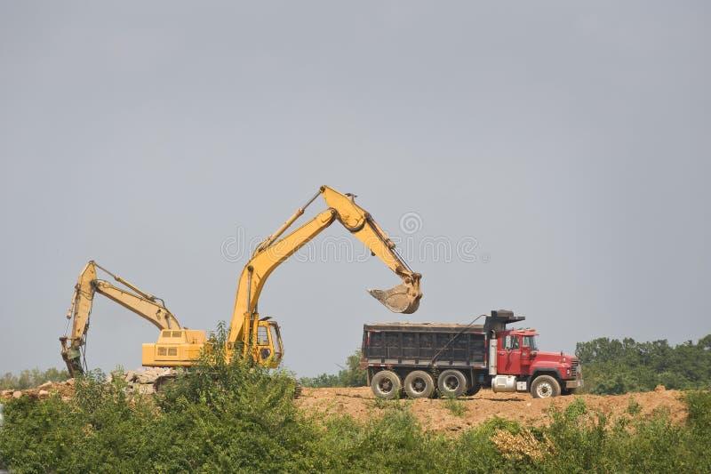 Loading a Dump Truck. A shovel loads a dump truck at a construction site stock photos
